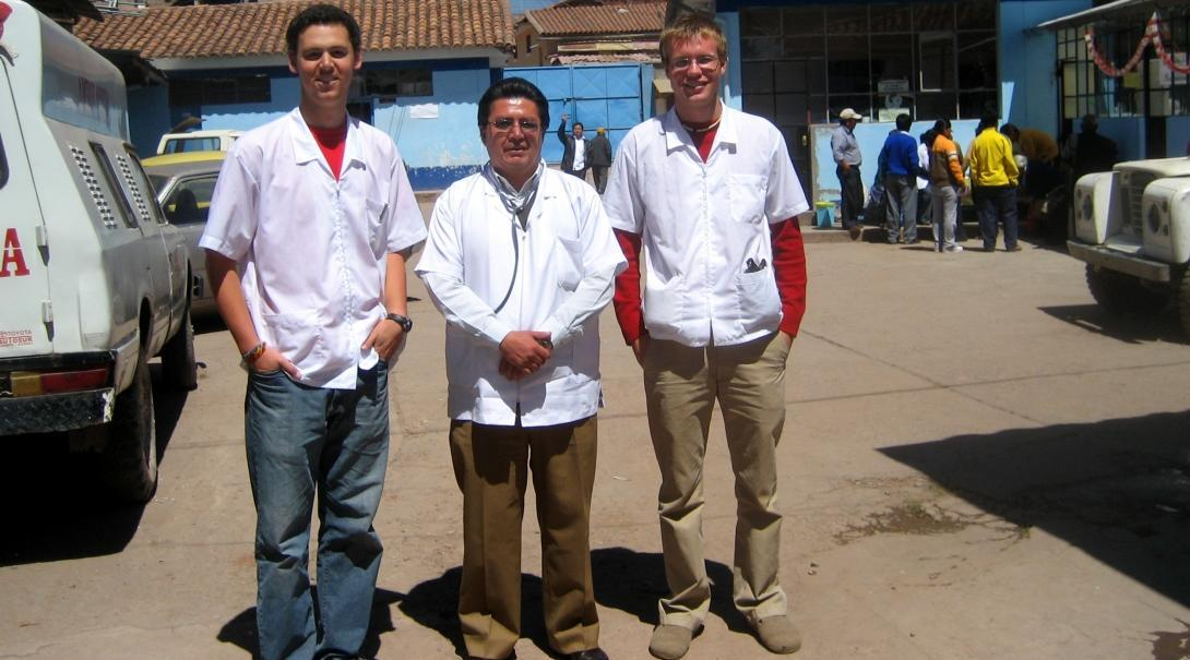 Two male interns with Projects Abroad take a picture with a local doctor outside the hospital during their nursing internship in Peru.